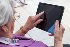 Alte Frau schreibt auf einen Tablet-PC stockbilder