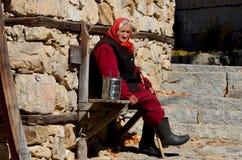 Alte Frau sitzen entlang Steinwand lizenzfreie stockfotografie