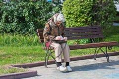 Alte Frau sitzt auf der Bank und entwirrt ein Kreuzworträtsel im Park in Wolgograd Lizenzfreie Stockbilder