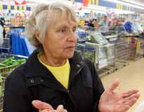 Alte Frau steht in einem Supermarkt hilflos stockbilder