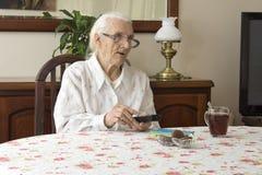 Alte Frau am Tisch mit Fernbedienung für das Fernsehen Lizenzfreies Stockfoto