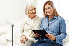 Alte Frau und Tochter, die Fotoalbum betrachtet lizenzfreies stockfoto