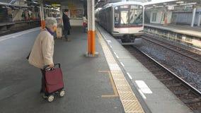 Alte Frau wartet auf einen Zug, um in Tokyo, Japan anzukommen lizenzfreies stockbild