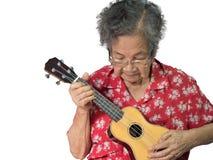 Alte Frau, welche die Ukulele spielt Lizenzfreies Stockbild