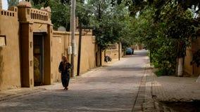 Alte Frauen des Uighur und Wohngebäude in Korla Lizenzfreies Stockfoto