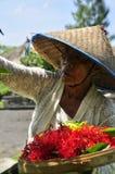Alte Frauen mit dem asiatischen Hut, der den Göttern Angebote unterbreitet Lizenzfreies Stockfoto