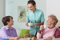 Alte Frauen, Tee und Krankenschwester Stockfoto