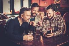 Alte Freunde, die Spaß mit Smartphone haben und Fassbier in der Kneipe trinken Stockbild