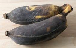 Alte Frucht der Bananen-zwei auf einem hölzernen Brett Lizenzfreie Stockfotografie