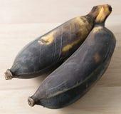 Alte Frucht der Bananen-zwei auf einem hölzernen Brett Stockfotos