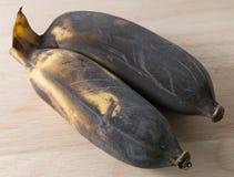 Alte Frucht der Bananen-zwei auf einem hölzernen Brett Lizenzfreies Stockfoto