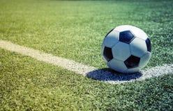 Alte Fußballkugel auf dem Gras Lizenzfreies Stockfoto