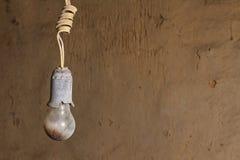 Alte gebrannte Birne gegen einen Hintergrund knackte Wand Stockfoto