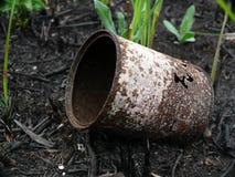 Alte gebrannte rostige Blechdose unter einem jungen Gras Stockfotos