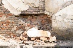 Alte gebrochene Backsteinmauer mit großen Stücken Gips Stockfotografie