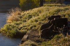 Alte gebrochene Bank auf Sonnenuntergang im Park Stockbilder