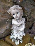 Alte gebrochene Engelsstatue mit blauen Augen Stockfotografie