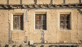 Alte gebrochene hölzerne Fenster auf einem verlassenen rustikalen Haus gemacht vom Holz und vom Lehm Stockfotografie