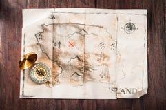 Alte gebrochene Karte der gefälschten Weinlese auf hölzernem Schreibtisch mit Kompass Piraten-Schatz-Karte Stockfotografie