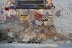 Alte gebrochene Wand des abstrakten Schmutzhintergrundes, Gips, der, an der Spitze des Metallfensters, roten der Stellen-, Blauen Stockfotos