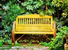 Alte gelbe Holzbank im Garten Abbildung der roten Lilie Stockfotografie