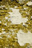 Alte gelbe Wand mit Sprüngen und Änderungen am Objektprogramm des Pflasters Stockfoto