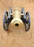 Alte gelbes Metallkanone mit schwarzen Rädern auf dem Sand im Freien Stockbild
