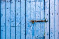 Alte gemalte blaue Tür mit Schieberiegel Stockfotografie