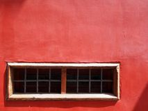 Alte gemalte rote Betonmauer mit schmalem Weiß gestaltete Fenster Stockfotografie