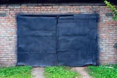 Alte gemalte schwarze Farbe auf Garage in der Natur Schwarze Tür in einem Gebäude gegen eine Backsteinmauer Ein grüner Rasenweg f Lizenzfreies Stockbild