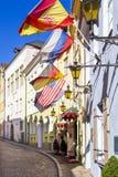 Alte gepflasterte Straße mit Straßenlaterne und Flaggen von Deutschland, von USA, von Russland und von Spanien, hängend an den bu stockfotografie