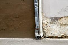 Alte geschädigte Wand- und Regengossenhintergrundbeschaffenheit Stockfoto