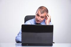 Alte Geschäftsmannblicke verwirrt am Laptop Stockfotos