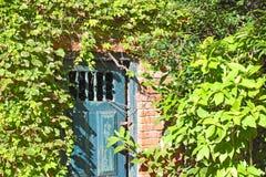 Alte geschlossene Tür in der Backsteinmauer Stockfotografie