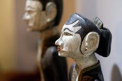 Alte geschnitzte Steinzahlen von Frauen und von Männern Stockbilder