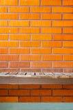 Alte getragene Bank auf einer Backsteinmauer Lizenzfreie Stockfotografie