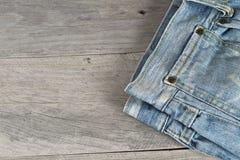 Alte getragene Jeans über einem hölzernen Hintergrund Lizenzfreies Stockbild