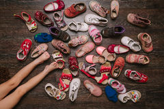 Alte getragene Schuhe des Babys (Kind, Kind) auf dem Boden Sandalen, Stiefel, s stockbilder