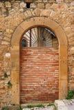 Alte gewölbte Tür geblockt durch Backsteinmauer Lizenzfreie Stockfotografie