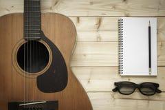 Alte Gitarre auf dem hölzernen Hintergrund Lizenzfreie Stockbilder