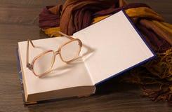 Alte Gläser, die auf dem Buch liegen Stockfotografie