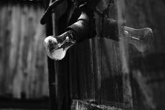 Alte Glühlampe mit Reflexion in defektem Glas auf hölzernem Wandhintergrund lizenzfreie stockfotografie