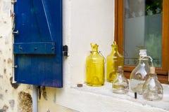Alte Glasflaschen im Fenster Stockfotografie