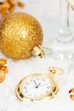 Alte goldene Uhr nah an Mitternacht und Weihnachtsdekorationen Stockfoto