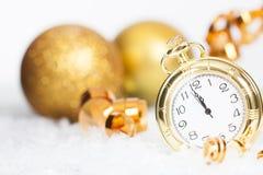 Alte goldene Uhr nah an Mitternacht und Weihnachtsdekorationen Lizenzfreie Stockbilder