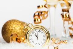 Alte goldene Uhr nah an Mitternacht und Weihnachtsdekorationen Stockbild