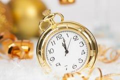 Alte goldene Uhr nah an Mitternacht und Weihnachtsdekorationen Lizenzfreie Stockfotos