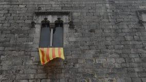 Alte gotische Fensterrealzeitfassade mit einer wellenartig bewegenden Flagge von Katalonien Catalunya bekannt als Senyera, gefang stock video footage