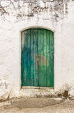 Alte grüne Bauholztür in der abgeriebenen Wand Stockfotografie