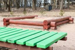 Alte grüne Holzbank und eine Sandgrube Stockfoto
